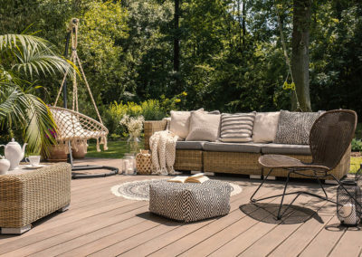 A rattan patio set including a sofa, a table and a chair on a wo